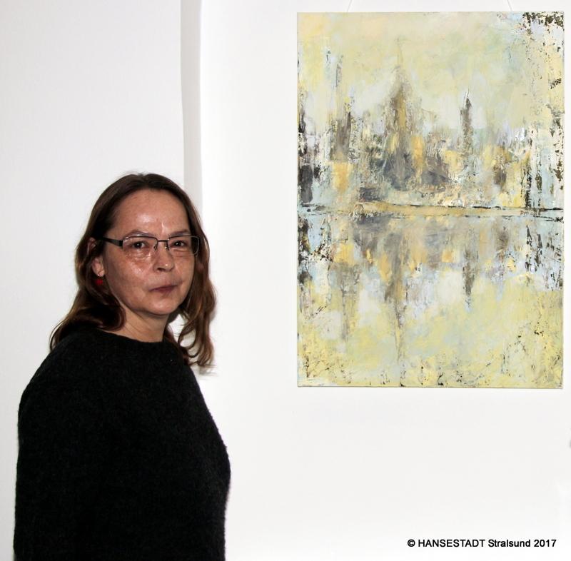 Diplom-Malerin und Grafikerin Grit Piolka vor ihrem Werk im Foyer des Rathauses